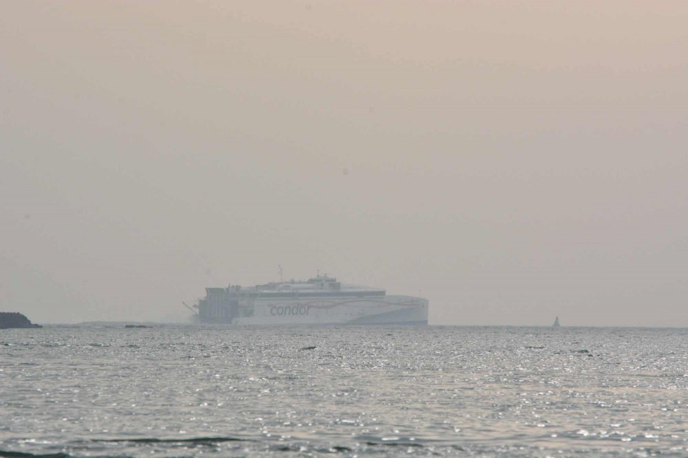 Liberation in the haze passing behind Elizabeth Castle on its way back to Guernsey and the UK.JPG