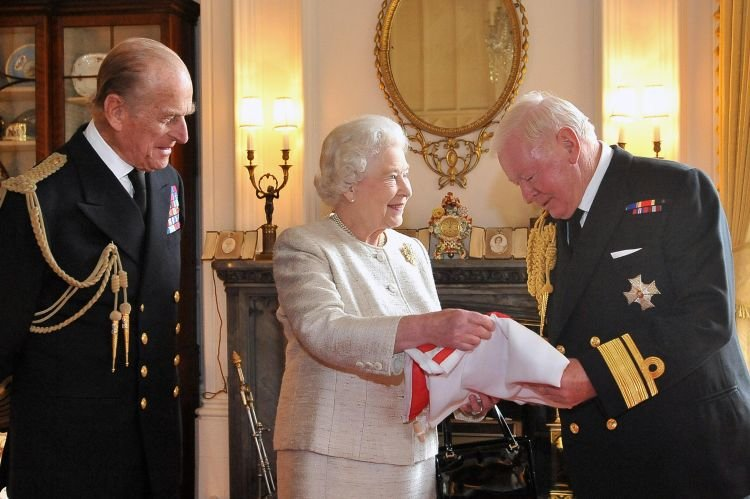 Prince Philip and the Queen presenting Sir Donald Gosling with a flag at Windsor Castle during a ceremony making him Vice Admiral of the UK 230412 CREDIT IAN NICHOLSON PA.jpg